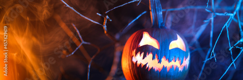 Fotografie, Obraz Spooky Halloween jack o lantern pumpkin with carved scary face glowing and billowing smoke in the night