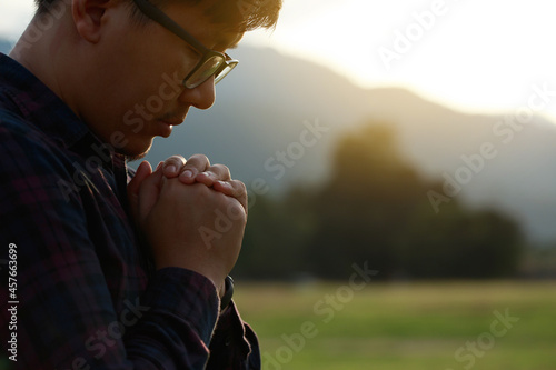 Leinwand Poster Religious man praying to God resting his chin on his hands in a field during a beautiful sunset