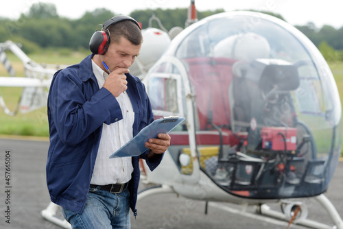 Canvas Print man looking at clipboard stood beside an autogyro