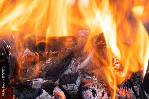 Canvastavla Close up of brightly burning wooden logs with yellow hot flames of fire at night