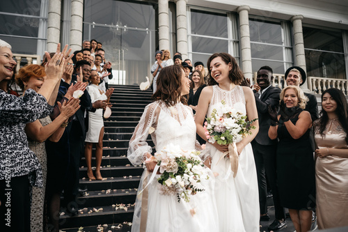 Foto Candid shot of two female lesbian LGBT brides walking down the stairs during the