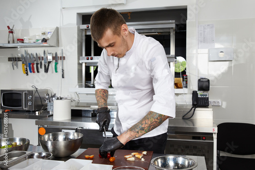 Murais de parede Professional chef cooking in the modern kitchen in hotel restaurant, preparing s