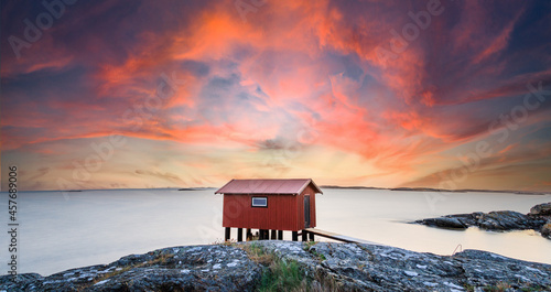 Fotografiet a colorful sunset of a red little fisherman's hut at the coast of sweden