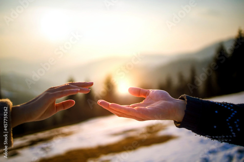 Fotografie, Obraz Young couple touching hands on the top of mountain on sunny winter day