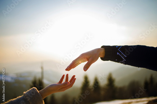 Fototapeta Young couple touching hands on the top of mountain on sunny winter day