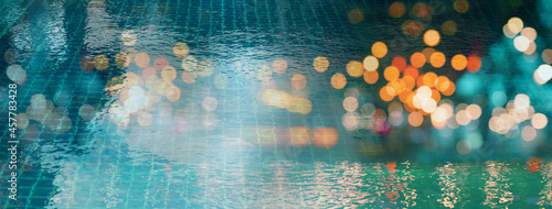 Obraz na plátně blur light of bar or pub reflection on blue water swimming pool summer party at