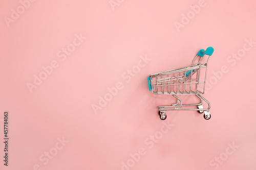 Fototapeta close-up the shopping trolley cart on a pink background with copy space for mark