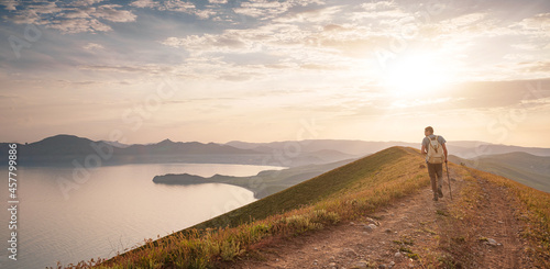 Canvas Print Young man travels alone walking on trail and enjoying on view of mountains and sea landscape at sunset , the lifestyle concept of traveling outdoors