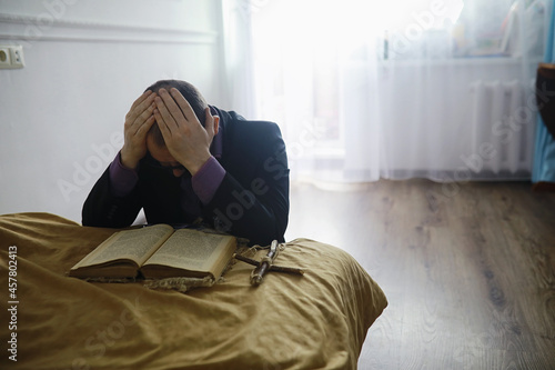 Foto Man reading and pray from the holy bible near the bed in the evening