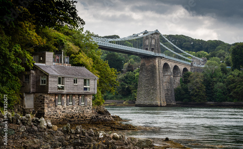 Leinwand Poster Menai suspension bridge in North Wales with boathouse in foreground on a gloomy