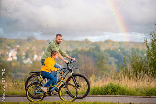 Платно Happy father and daughter take bike ride in nature in autumn.