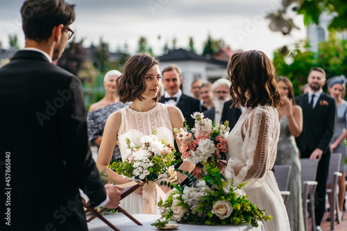 Canvas Portrait of two loving female lesbian LGBT brides telling their marriage vows at the wedding ceremony in front of wedding officiant