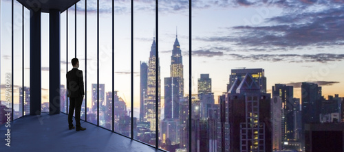Fotografiet Businessperson in empty office looking out of panoramic window with bright city downtown and sky view with mock up place