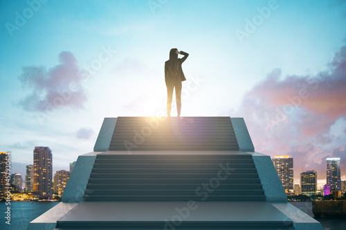 Fotografia Back view of young european businesswoman standing on top of stairs on bright city background with sky view