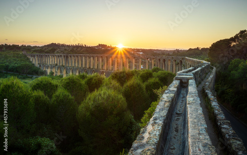 Leinwand Poster View over the Pegões aqueduct with a beautiful sunset in the background, near the city of Tomar in Portugal