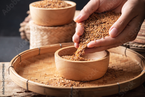 Obraz na plátně Brown flax seed holding by hand and pouring in a bowl on bamboo tray