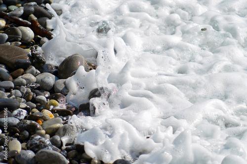 Schiuma sulle pietre del mare. Fine di un'onda