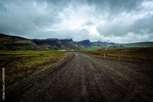 Driving on an unpaved road in summer in Iceland, moutains landscape, moody sky with dark clouds