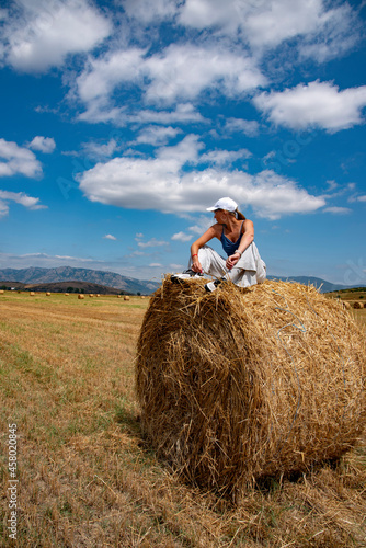 Canvastavla A girl is sitting on a haystack in a huge field against the background of mountains on a sunny August day
