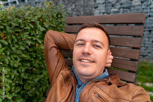 Handsome man relaxing on wooden chaise lounge in city park Fototapeta