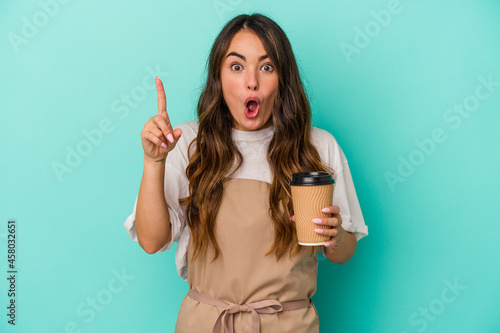 Tela Young caucasian store clerk woman holding a takeaway coffee isolated on blue background having an idea, inspiration concept