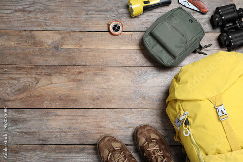 Fotografering Flat lay composition with tourist backpack and other camping equipment on wooden