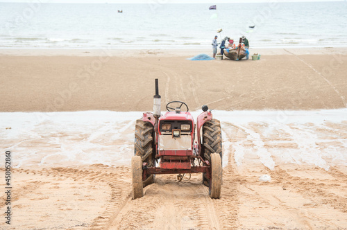 Carta da parati Tractors waiting to haul a local fishing boat out of the sea at low tide at Jomt