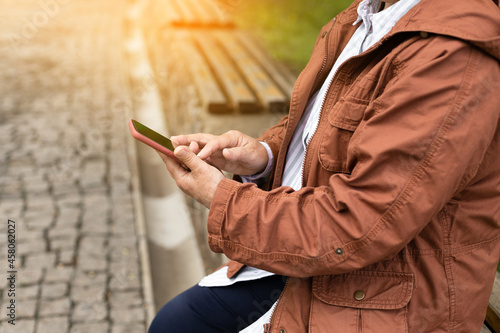 Fotografia Cropped shot of smiling young woman using her mobile phone, reading messages on