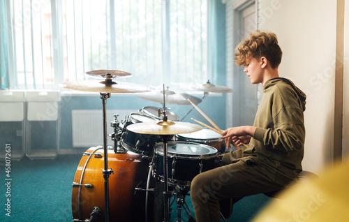 Boy musician behind a drum kit. Fotobehang