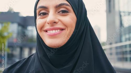 Canvas Print close up of joyful muslim woman in hijab woman looking at camera outside