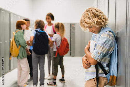Lonely sad schoolboy crying while all his classmates ignoring him Fototapet