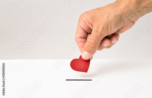 Murais de parede Red heart symbol is put by person's hand into slot of white donation box