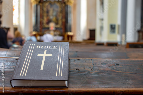 Fotografiet The Bible on the table of a prayer bench in the church with a altar
