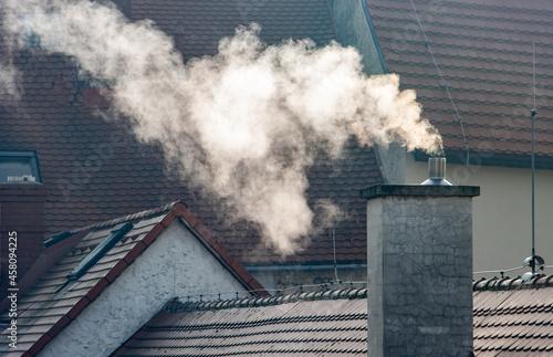 Billede på lærred Smoke rising from the chimney in city