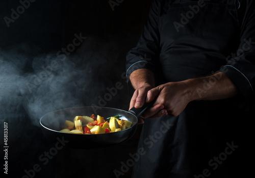 Cook prepares vegetables in a frying pan Fototapet