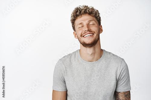 Fotografiet Handsome smiling blond man close eyes, daydreaming, imaging something, having ha