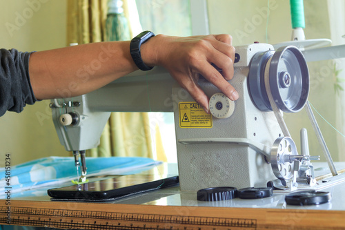 close up of a hand setting and repairing an electric sewing machine using a scre Fototapeta