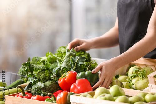 Obraz na plátně Female seller with fresh vegetables in market