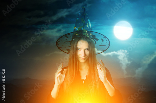 Fototapeta Halloween witch cooking potion,magical sorceress in a hat at midnight on backgro