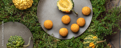 Foto Decorative small pumpkins and cheese crockets on grey stoneware plates  on green