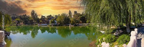 Fotografija a stunning panoramic shot of a Japanese garden with deep green lake water and lu