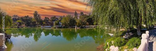 a stunning panoramic shot of a Japanese garden with deep green lake water and lu Fototapeta