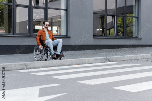 Photographie young handicapped man sitting in wheelchair near border and crosswalk