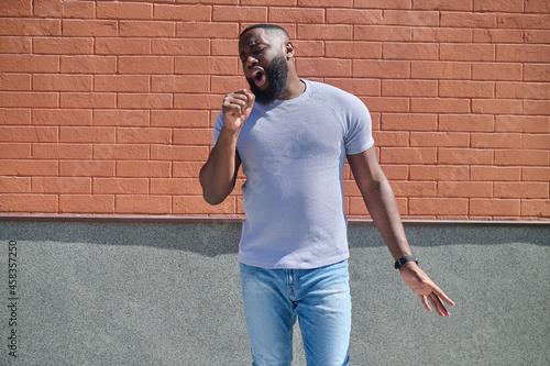 A dark-skinned man in a white tshirt and jeans feeling good Fototapet