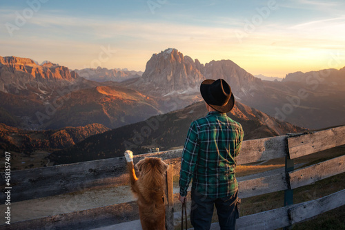 a man with dog looking at the mountains Fototapet