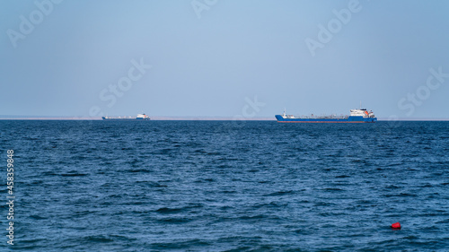 Obraz na plátně Two large transport ships are in the roadstead in the sea bay against the backgr