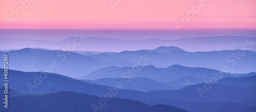 Fotografia Mountain ridges in fog and pink sky at sunset in autumn