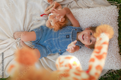 Fototapeta Niño jugando con sus peluches en el jardín