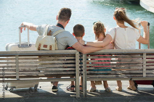 Canvas-taulu Back view of traveling happy family of four relaxing on embankment with suitcase