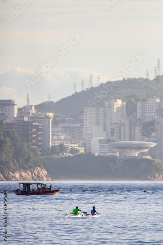 Fototapeta People In Sea By City Against Sky